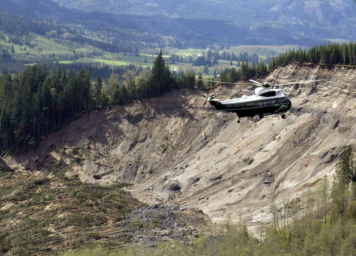Marine One helicopter, carrying President Barack Obama, takes an aerial tour of Oso on Tuesday, April 22, 2014 above the site of the deadly mudslide that struck the community in March.