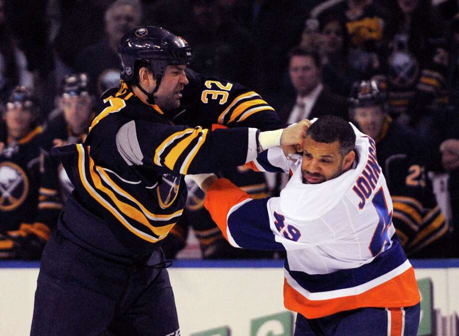 Buffalo Sabres left winger John Scott (32) lands a punch to the side of the head on New York Islanders right winger Justin Johnson (49) during the first period of an NHL hockey game in Buffalo, N.Y., Sunday April 13, 2014. (AP Photo/Gary Wiepert) Photo: Gary Wiepert, Associated Press / Associated Press