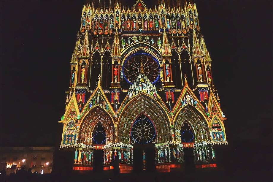 A free light show on summer evenings gives an idea of what the Reims Cathedral looked like when it was painted in the 13th century. Photo: Rick Steves, Rick Steves' Europe