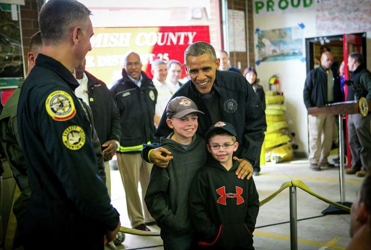 President Barack Obama poses for a photo with Landon Harper, 9, and Levi Harper, 7, sons of Oso Fire Chief Willy Harper, as the president visits the Oso Fire Station. He greeted and spoke with rescuers there, near the scene of last month's deadly Oso mudslide. Photographed on Tuesday, April 22, 2014.