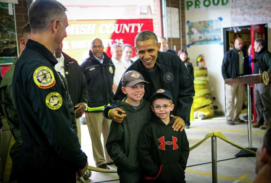 President Barack Obama poses for a photo with Landon Harper, 9, and Levi Harper, 7, sons of Oso Fire Chief Willy Harper, as the president visits the Oso Fire Station. He greeted and spoke with rescuers there, near the scene of last month's deadly Oso mudslide. Photographed on Tuesday, April 22, 2014. Photo: JOSHUA TRUJILLO, SEATTLEPI.COM / SEATTLEPI.COM