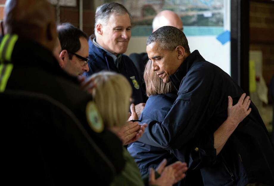 President Barack Obama hugs Arlington Mayor Barbara Tolbert as he visits the Oso Fire Station where he greeted and spoke with rescuers near the scene of last month's deadly Oso mudslide. Photo: JOSHUA TRUJILLO, SEATTLEPI.COM / SEATTLEPI.COM
