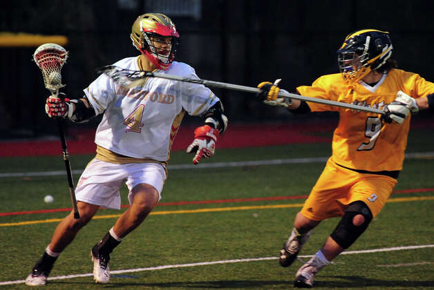Stratford's Isaiah Booker, left, drives the ball as Weston's Jackson Catalano tries to block, during boys lacrosse action at Penders Field in Stratford, Conn. on Tuesday April 22, 2014. Photo: Christian Abraham / Connecticut Post