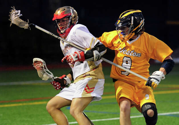 Weston's Jackson Catalano tries to block Stratford's Isaiah Booker, left, during boys lacrosse action at Penders Field in Stratford, Conn. on Tuesday April 22, 2014. Photo: Christian Abraham / Connecticut Post