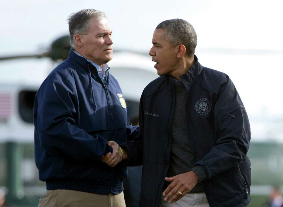 President Barack Obama shakes hands with Washington Gov. Jay Inslee as he turns to board Air Force One at Paine Field Airport, Tuesday, April 22, 2014, in Everett, Wash., after visiting Oso, Wash., the site of the deadly mudslide that struck the community in March. The president is en route to a four-country trip through the Asia-Pacific region. Photo: Carolyn Kaster, ASSOCIATED PRESS / AP2014
