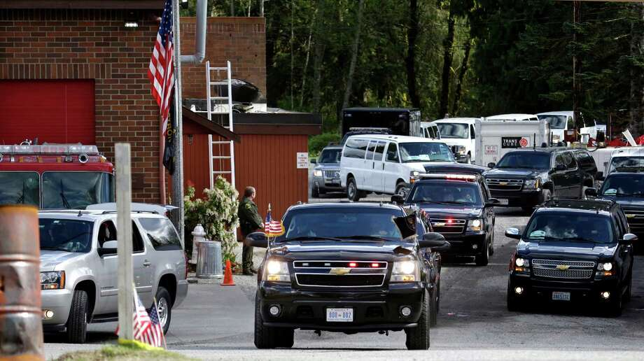 President Barack Obama's motorcade departs the Oso fire station, its flag still flying at half-staff at left, after he met with emergency responders Tuesday, April 22, 2014, in Oso, Wash. Obama was visiting the area about an hour northeast of Seattle to survey damage from a recent mudslide nearby that killed more than three dozen people. The deadly March 22 mudslide killed at least 41 people and buried dozens of homes.  Photo: Elaine Thompson, ASSOCIATED PRESS / AP2014