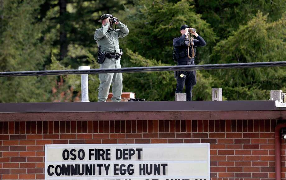Security personnel look out from atop the Oso fire station as President Barack Obama's motorcade nears the area Tuesday, April 22, 2014, in Oso, Wash. Obama was visiting the area about an hour northeast of Seattle to survey damage from a recent mudslide nearby that killed more than three dozen people. The deadly March 22 mudslide killed at least 41 people and buried dozens of homes. Photo: Elaine Thompson, ASSOCIATED PRESS / AP2014