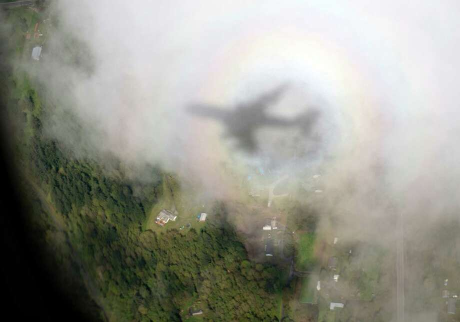 The shadow of Air Force One, with President Barack Obama aboard, is seen on a cloud as it approaches Paine Field Airport, Tuesday, April 22, 2014, in Everett, Wash., en route to Oso, Wash., the site of the deadly mudslide that struck the community in March. Photo: Carolyn Kaster, ASSOCIATED PRESS / AP2014
