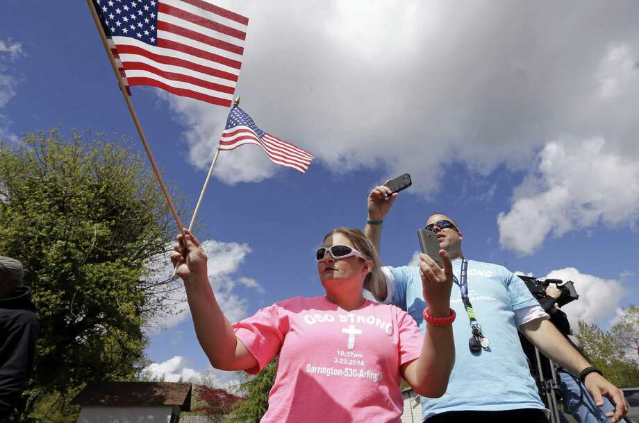 Brande Taylor, left, and her partner Matt Ingison wave flags and take photos as President Barack Obama's motorcade drives past Tuesday, April 22, 2014, in Oso, Wash. Obama was visiting the area about an hour northeast of Seattle to survey damage from a recent mudslide nearby that killed more than three dozen people. The deadly March 22 mudslide killed at least 41 people and buried dozens of homes. Photo: Elaine Thompson, ASSOCIATED PRESS / AP2014