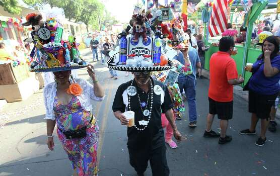 Dora Gonzales (from left), Albert Limon, and Pauleen Gonzales stroll around La Villita with their finely adorned fiesta sombreros at the kickoff of 2014 Night In Old San Antonio (NIOSA) on Tuesday, Apr. 22, 2014. Photo: Kin Man Hui, San Antonio Express-News / ©2014 San Antonio Express-News