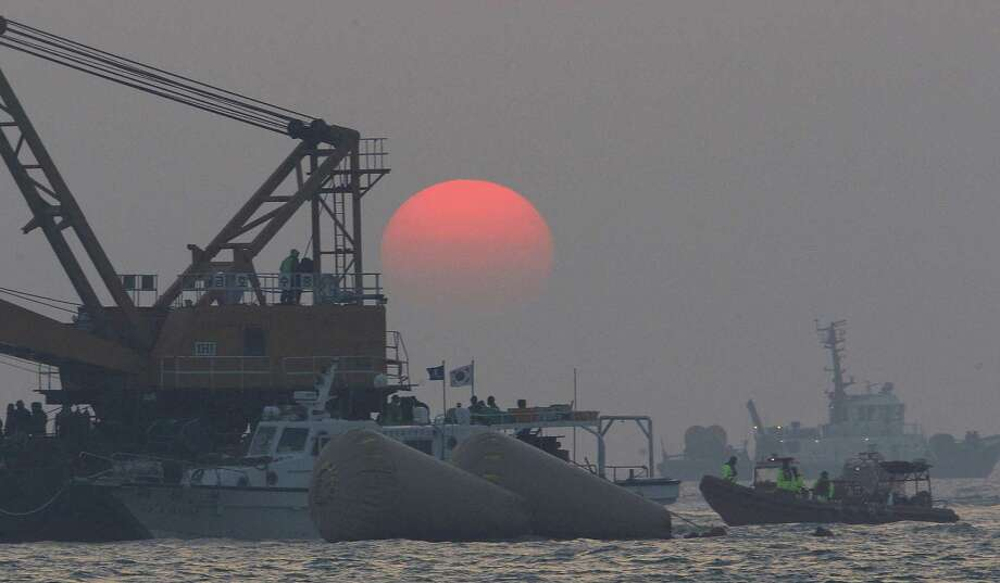 As the sun sets, divers look for bodies of passengers believed trapped in the sunken ferry Sewol in the water off the southern coast near Jindo, south of Seoul, South Korea. Photo: Ahn Ung-joon / Associated Press / AP