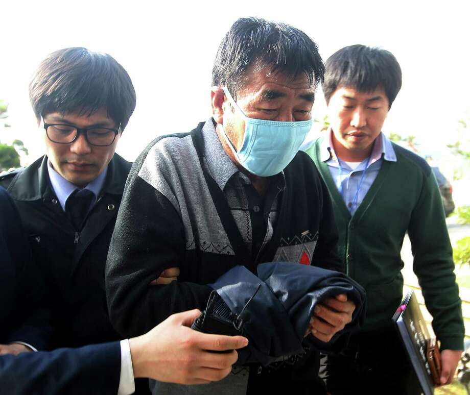 "FILE - In this April 19, 2014 file photo, Lee Joon-seok, center, the captain of the sunken ferry boat Sewol in the water off the southern coast, arrives at the headquarters of a joint investigation team of prosecutors and police in Mokpo, south of Seoul, South Korea. Nearly a week after the sinking of the South Korean ferry, with rising outrage over a death count that could eventually top 300, the public verdict against the crew of the Sewol has been savage and quick. ""Cowards!"" social media users howled. ""Unforgivable, murderous,"" President Park Geun-hye said Monday of the captain and some crew. (AP Photo/Yonhap, File) KOREA OUT ORG XMIT: TOK803 Photo: Uncredited / Yonhap"