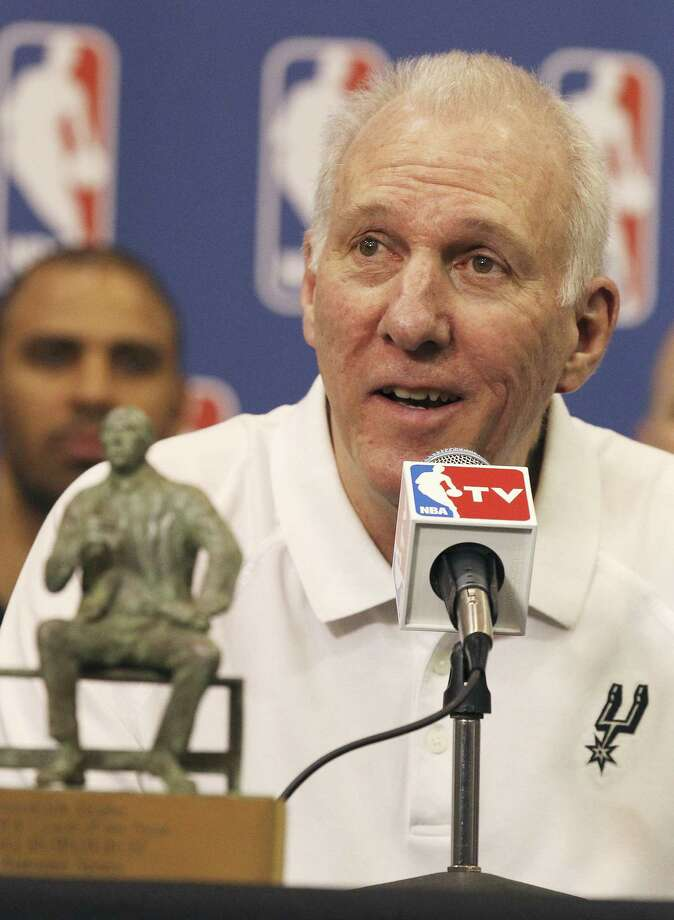 Gregg Popovich, with the Red Auerbach trophy, addresses the media after being named Coach of the Year, joining Don Nelson and Pat Riley as those who have been honored three times. Photo: Kin Man Hui / San Antonio Express-News / ©2014 San Antonio Express-News