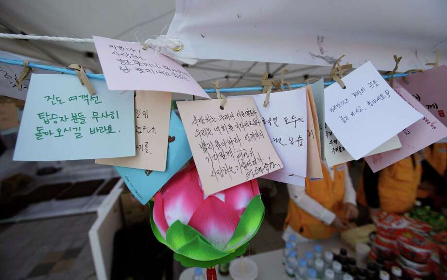 Messages wishing safe return of passengers aboard the sunken ferry Sewol hang with a Buddhism lotus decoration in Jindo, south of Seoul, South Korea, Tuesday, April 22, 2014. One by one, coast guard officers carried the newly arrived bodies covered in white sheets from a boat to a tent on the dock of this island, the first step in identifying a sharply rising number of corpses from a South Korean ferry that sank nearly a week ago. (AP Photo/Lee Jin-man) Photo: Lee Jin-man, STF / AP