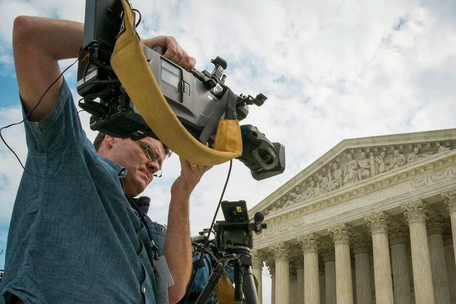 A videojournalist sets up outside of the Supreme Court in Washington, Tuesday, April 22, 2104. The court is hearing oral arguments between Aereo, Inc., an Internet startup company that gives subscribers access to television on their laptops and other portable devices and the over-the-air broadcasters. (AP Photo/J. David Ake) Photo: J. David Ake, STF / AP