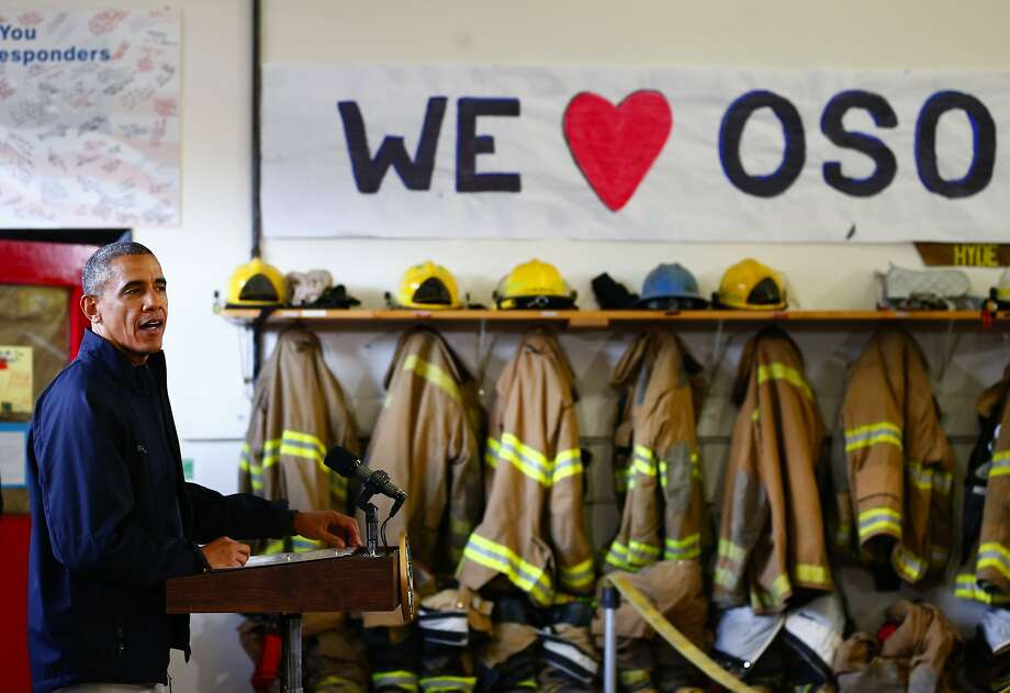 President Barack Obama, left, makes his remarks inside the Oso Fire Department after surveying the damage and response efforts on Tuesday, April 22, 2014, in Oso, Wash, one month after a massive mudslide that killed 41 people. As of Tuesday, 41 victims have been identified, with the missing list narrowed down to just two. (AP Photo/The Seattle Times, Lindsey Wasson, Pool) Photo: Lindsey Wasson, Associated Press
