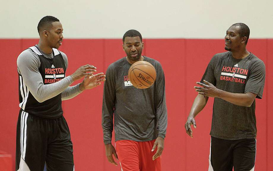 Rockets center Dwight Howard, left, works out with Hakeem Olajuwon, right, and assistant coach Derrick Alston at Tuesday's practice. Photo: James Nielsen, Staff / © 2014  Houston Chronicle