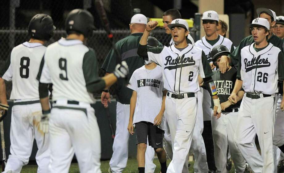 Reagan players congratulate teammate Jack Thompson (far left) after scoring a run during the Rattlers' 3-1 victory over Churchill on Tuesday at Blossom Athletic Center. Photo: Darren Abate / For The Express-News