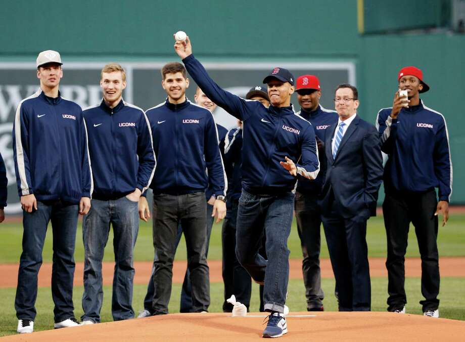Connecticut men's basketball team members watch teammate,Shabazz Napier throw a ceremonial first pitch prior to a baseball game between the Boston Red Sox and the New York Yankees at Fenway Park in Boston, Tuesday, April 22, 2014. At second from right is Connecticut Gov. Dannel P. Malloy. The team won the NCAA men's college basketball tournament. (AP Photo/Elise Amendola) Photo: Elise Amendola, Associated Press / Associated Press