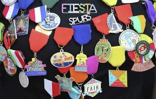 Fiesta medals such as these from Juanita Chavez are given, traded and sold for a myriad of causes. Photo: Photos By Edward A. Ornelas / San Antonio Express-News / © 2014 San Antonio Express-News