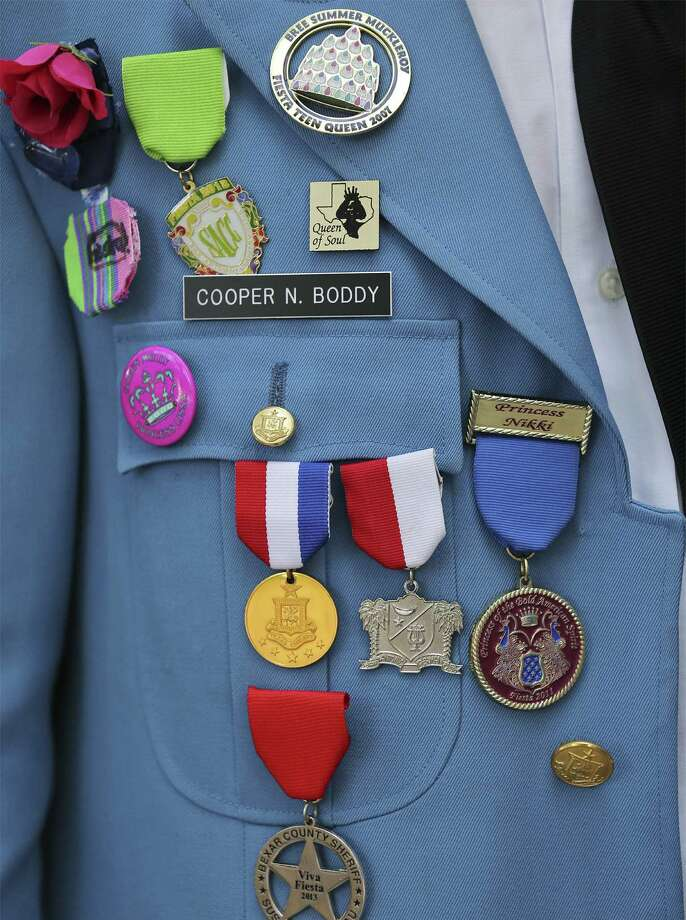 Companies producing the medals, such as these worn by Cooper N. Boddy, estimate that there could be more than 1,000 different kinds this Fiesta. / © 2014 San Antonio Express-News
