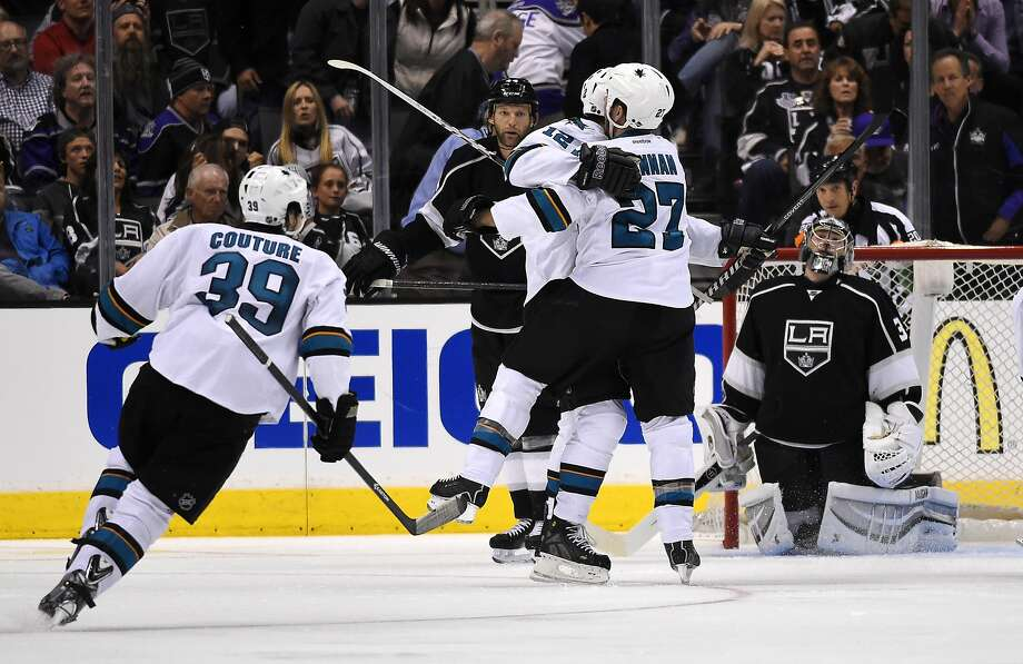 Patrick Marleau (12) and Scott Hannan embrace, and Logan Couture is about to join them, after Marleau's game-winning goal. Photo: Mark J. Terrill, Associated Press