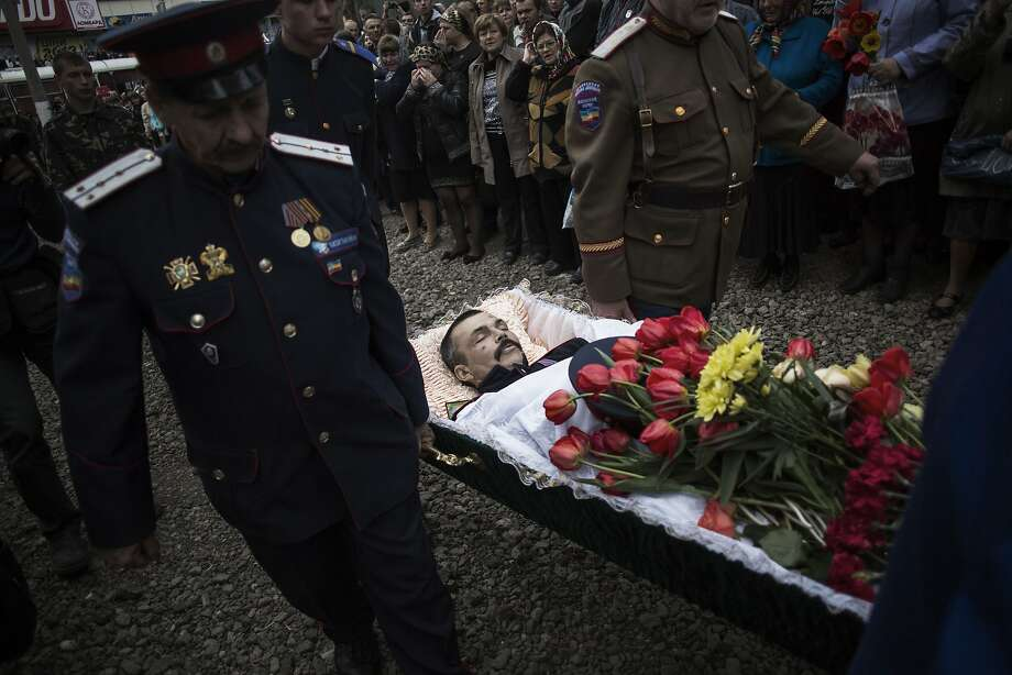 The body of Pavel Pavelco, 42, a pro Russia militiaman, one of three people killed last Sunday in a shooting by unknown gunmen at a checkpoint, is carried by pallbearers to a church during a funeral in Slovyansk, Ukraine, Tuesday, April 22, 2014. (AP Photo/Manu Brabo) Photo: Manu Brabo, Associated Press