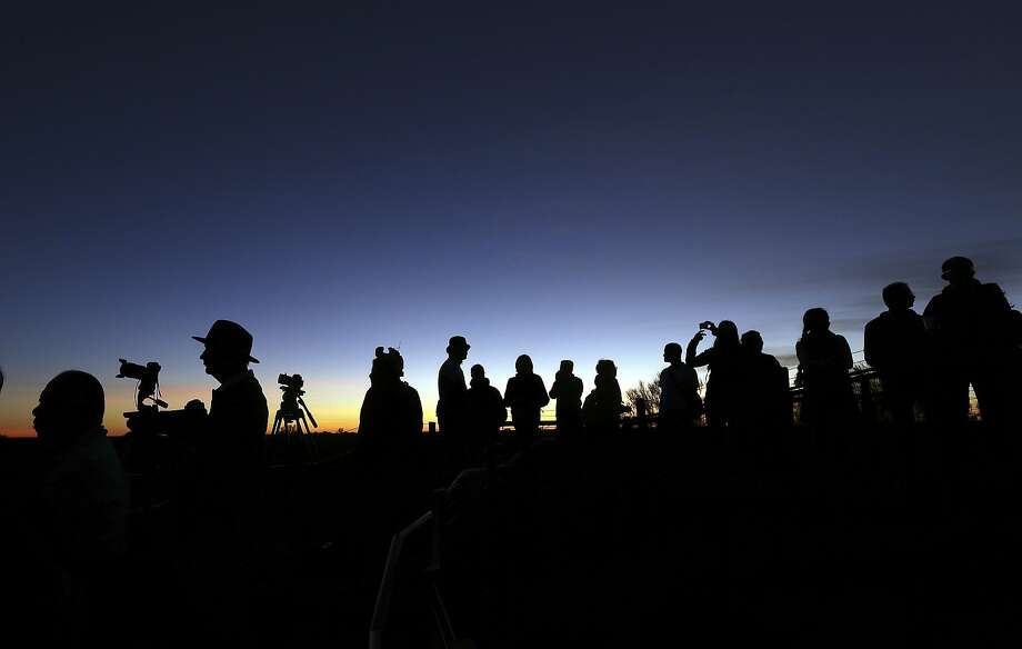 Tourists stand on a viewing platform to watch the sunrise in Uluru, Australia, Tuesday, April 22, 2014. The Duke and Duchess of Cambridge will visit Uluru, also known as Ayers Rock, Tuesday during their three-week tour of Australia and New Zealand, the first official trip overseas with their son, Prince George. (AP Photo/Rob Griffith) Photo: Rob Griffith, Associated Press