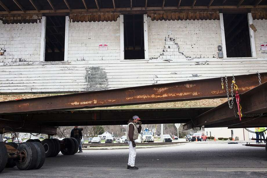 A team of Fruitport contractors overseen by Dave Joneson maneuver the 119 year old Clare Railroad Depot over a curb to its new downtown Clare location on Tuesday, April 22, 2014. (AP Photo/Midland Daily News, Zack Wittman) Photo: Zack Wittman, Associated Press