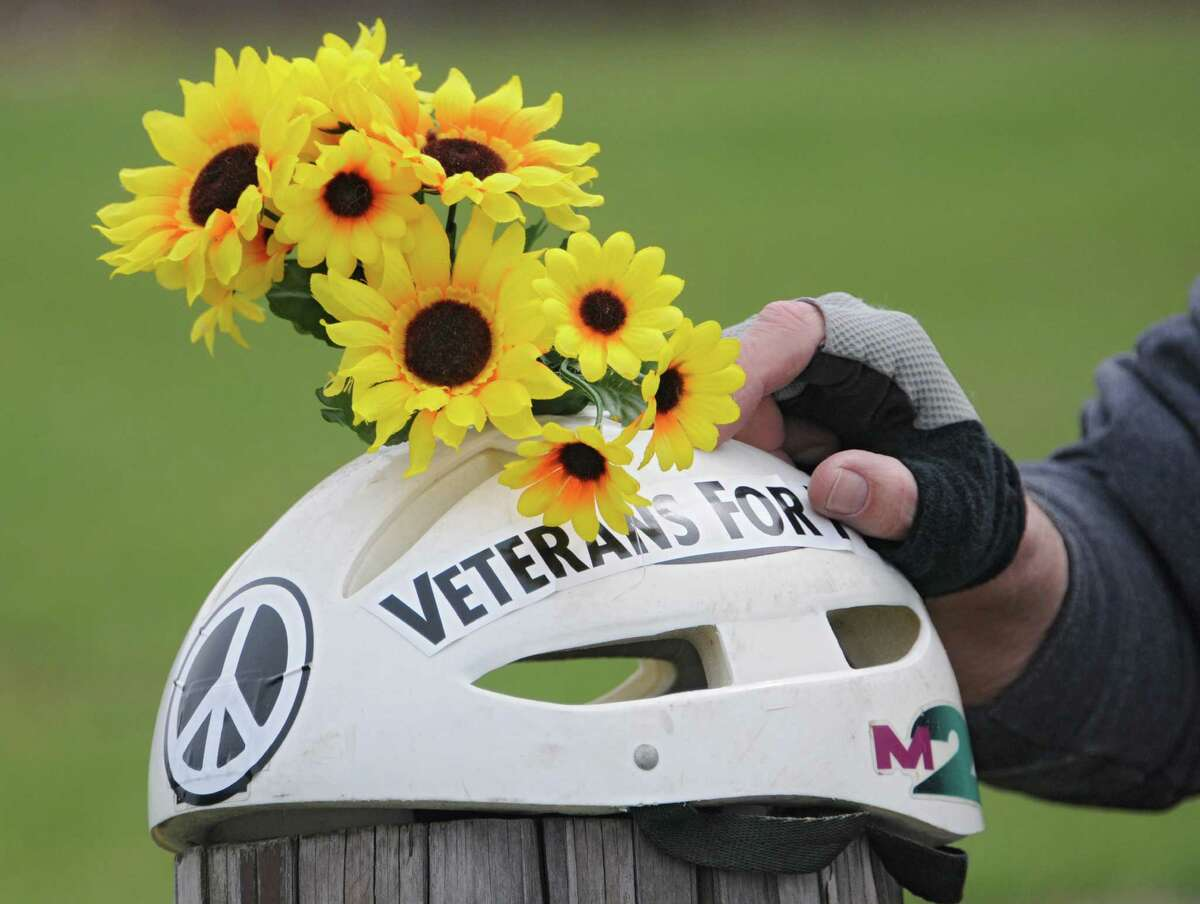 Dan Wilcox of Albany rest his hands on his bike helmet decorated with flowers while waiting in Tivoli Park to participate in a bike parade to celebrate Earth Day on Tuesday, April 22, 2014 in Albany, N.Y. (Lori Van Buren / Times Union)