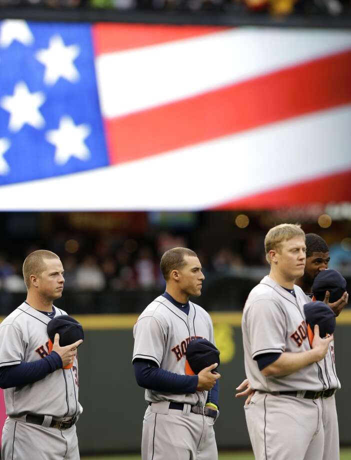 Astros players, including Matt Dominguez, left, and Pat Listach, second from left, stand during the national anthem. Photo: Ted S. Warren, Associated Press