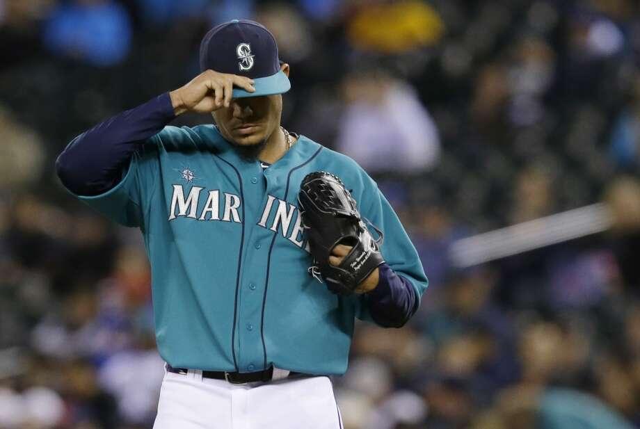 Mariners starting pitcher Felix Hernandez adjusts his cap. Photo: Ted S. Warren, Associated Press