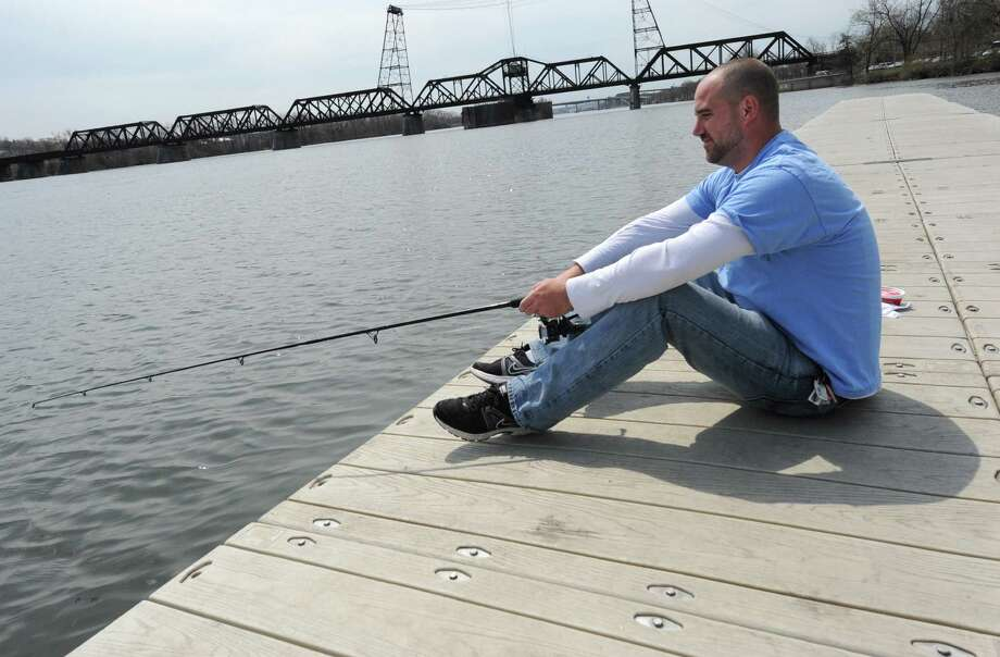 Robert Shaylor of Glenville sits on a dock to fish at the Corning Preserve Tuesday, April 22, 2014 in Albany, N.Y. (Lori Van Buren / Times Union) Photo: Lori Van Buren, Albany Times Union