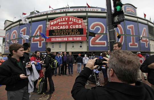 In this April 10, 2014 photo, fans arrive at Wrigley Field before a baseball game between Pittsburgh Pirates and Chicago Cubs in Chicago. Wrigley Field will host its 100th anniversary celebration as the Chicago Cubs host the Arizona Diamondbacks, exactly one century after the Chicago Federals opened then-Weeghman Park against the Kansas City Packers. (AP Photo/Kiichiro Sato) Photo: Kiichiro Sato, ASSOCIATED PRESS