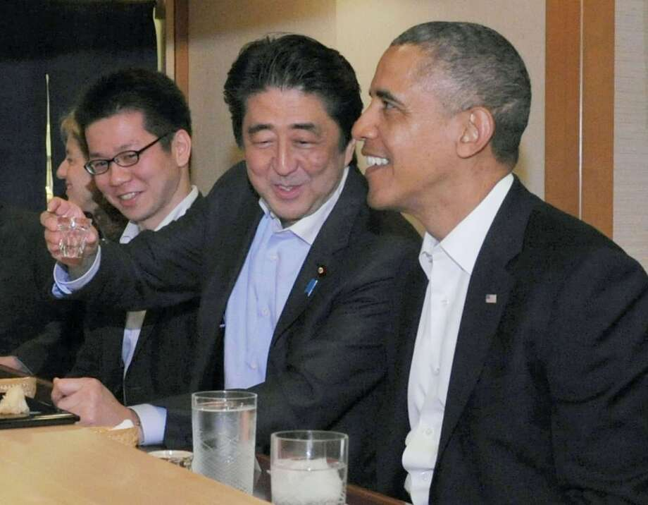 U.S. President Barack Obama (R) talks with Japan's Prime Minister Shinzo Abe during dinner at Sukiyabashi Jiro sushi restaurant in Tokyo's Ginza district, in this photo taken by Japan's Cabinet Public Relations Office and released by Kyodo April 23, 2014. Photo: KYODO, Reuters