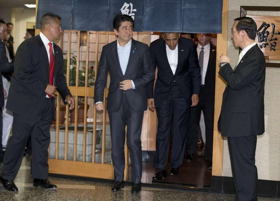 President Barack Obama and Japanese Prime Minister Shinzo Abe leave after having  dinner at Sukiyabashi Jiro sushi restaurant in Tokyo. Photo: Carolyn Kaster, Associated Press