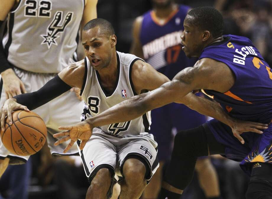 Spurs' Patty Mills (08) gets defended by Phoenix Suns' Eric Bledsoe (02) in the first half at the AT&T Center on Friday, Apr. 11, 2014. Photo: Kin Man Hui, San Antonio Express-News