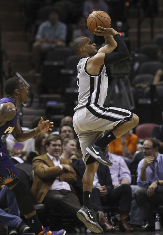 Spurs' Patty Mills (08) shoots a three against Phoenix Suns' Eric Bledsoe (02) in the first half at the AT&T Center on Friday, Apr. 11, 2014. Photo: Kin Man Hui, San Antonio Express-News