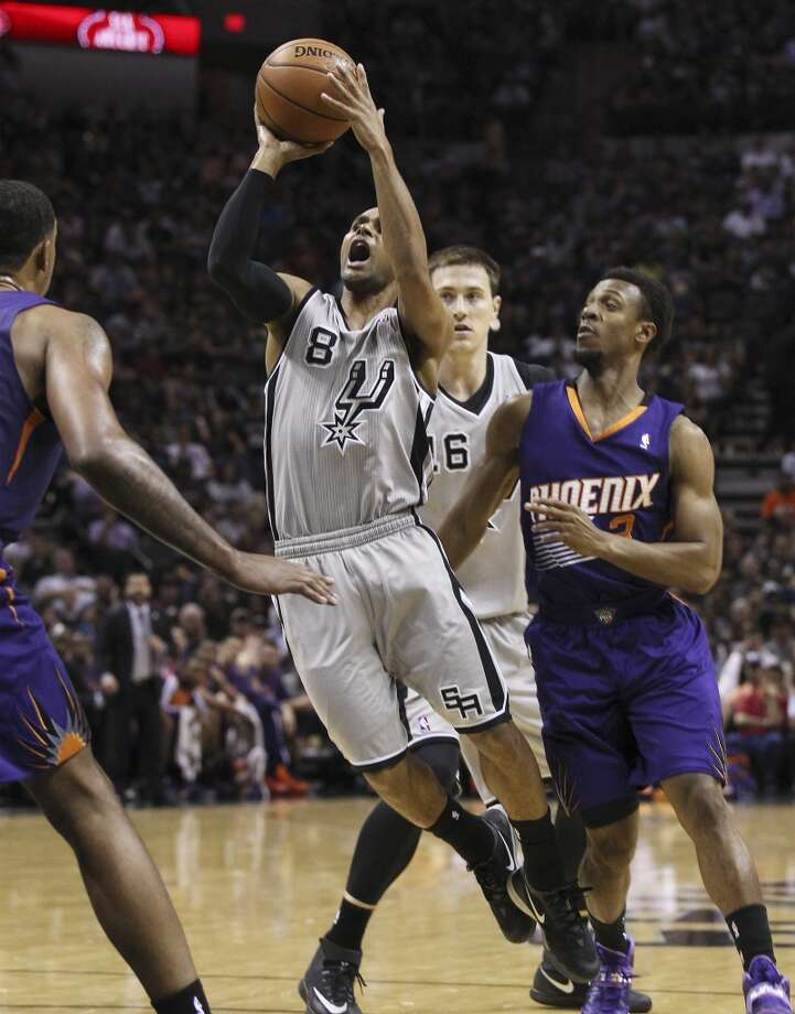 Spurs' Patty Mills (08) attempts a shot against Phoenix Suns' Ish Smith (03) in the first half at the AT&T Center on Friday, Apr. 11, 2014. Photo: Kin Man Hui, San Antonio Express-News