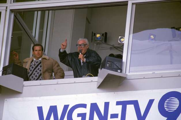 "Chicago Cubs baseball announcer and Baseball Hall of Fame inductee Harry Caray conducts fans singing ""Take Me Out to the Ball Game"" from his television booth as his partner Steve Stone looks on during the seventh inning stretch in a regular season game in May of 1989 at Wrigley Field in Chicago, Illinois. (Photo by Bernstein Associates/Getty Images) Photo: Bernstein Associates, Getty Images"