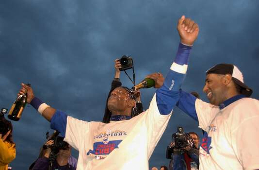 Right fielder Sammy Sosa #21 of the Chicago Cubs has champagne poured over him by coach Julian Martinez as they celebrate a win over the Pittsburgh Pirates that clinched the National League Central Division Championship after the second game of a double-header on September 27, 2003 at Wrigley Field in Chicago, Illinois.  The Cubs defeated the Pirates 7-2.  (Photo by Jonathan Daniel/Getty Images) Photo: Jonathan Daniel, Getty Images
