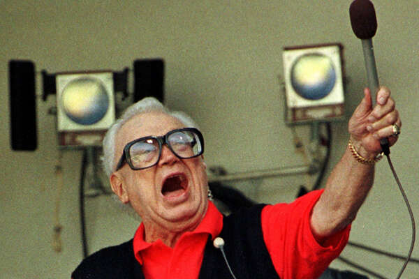 """Chicago Cubs baseball announcer and Baseball Hall of Fame inductee Harry Caray conducts fans singing """"Take Me Out to the Ball Game"""" from his television booth during the seventh inning stretch in this August 1997 file photo at Wrigley Field,."""