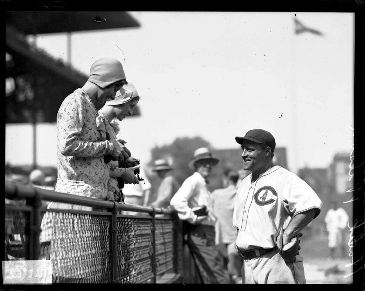 Chicago Cubs player Hack Wilson, speaking with two unidentified women in the stands at Wrigley Field, 1929.