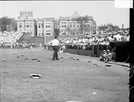 Man holding two boater hats, standing amid other boater hats that are lying on the field in front of crowd in grandstands at Wrigley Field during a World Series game between the National League's Chicago Cubs and the American League's Philadelphia Athletics, Chicago, Illinois, 1929. (Photo by Chicago History Museum/Getty Images) Photo: Chicago History Museum, Getty Images