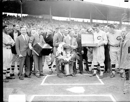 National League's Chicago Cubs baseball player Koehler, holding an open box or case, standing with a group of unidentified men at home plate during an awards ceremony at Wrigley Field, Chicago, Illinois, 1926. One of the men is holding a large floral arrangement. Cubs players are standing in the background and on the sides of the image. (Photo by Chicago History Museum/Getty Images) Photo: Chicago History Museum, Getty Images