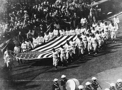 American professional baseball players of the American League New York Yankees and the National League Chicago Cubs carry an oversized novelty American flag into Wrigley Field before a game of the World Series, Chicago, Illinois, 1932. The Yankees won the Series four games to none. (Photo by Bruce Bennett Studio/Getty Images) Photo: B Bennett, Getty Images