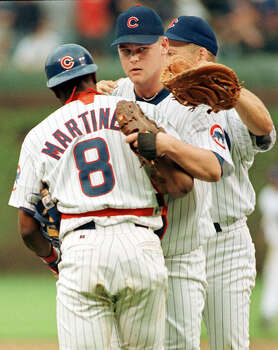 Pitcher Kerry Wood of the Chicago Cubs (C) is hugged by teammates Sandy Martinez (L) and Mark Grace (R) after his game against the Houston Astros 06 May at Wrigley Field in Chicago,IL. In his fifth major league start, he tied the major league record with 20 strikeouts to win the game 2-0.  (Photo credit should read DANIEL LIPPITT/AFP/Getty Images) Photo: DANIEL LIPPITT, AFP/Getty Images / AFP
