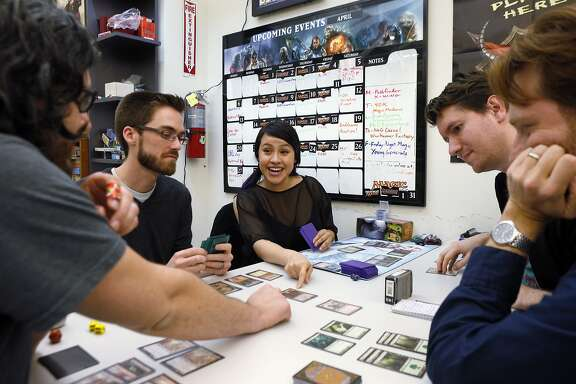 L-R, Mike Escalante, Elliot Morrow, Andi Morrow, Scott Goodenow, and Stewart McMaken play a game of Magic the Gathering at Endgame in Oakland, Calif., on Thursday, April 17, 2014. Endgame, which opened at its current location 10 years ago, sells only board and miniature games and thrives despite not offering video or electronic games. Now, the store is using a Kickstarter campaign to open a cafe that will open next to the main store in several months.