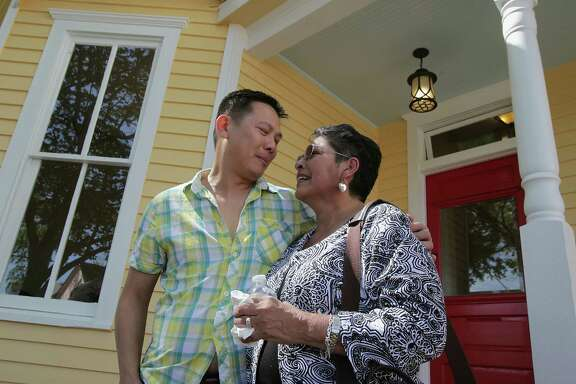 Dominic Yap, who is buying old homes in the First Ward but remodeling them instead of tearing them down, shows Gloria Perez the house she sold him. Yap renovated the interior and painted the exterior a sunny yellow.