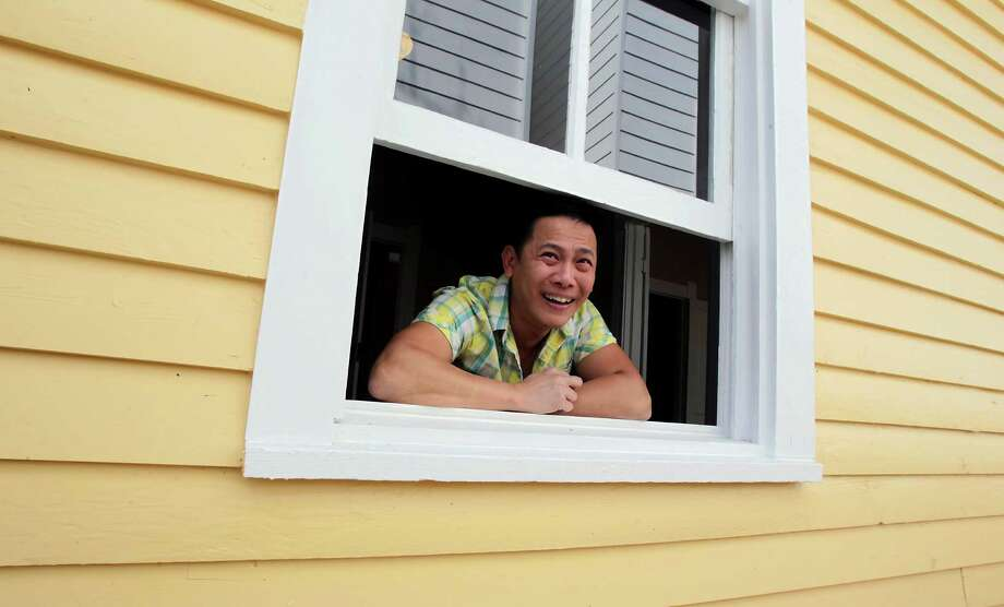 "Dominic Yap bought this home in the First Ward in 2013, anxious to try ""respectful restoration"" rather than demolition. In this photo he looks out the window of the home he purchased from Gloria  and Paul Perez. The job is finished...and in one day there was a contract on the home.